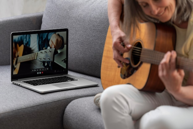 Senior vrouw thuis op de bank met laptop voor gitaarlessen