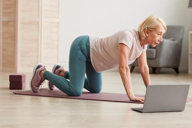 Senior vrouw trainen op de vloer voor laptop tijdens haar online training thuis