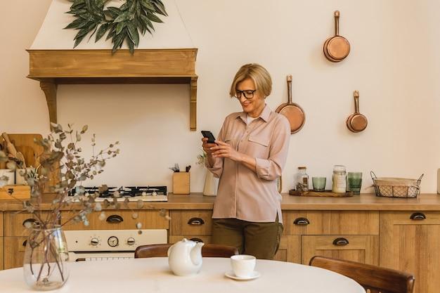 Senior vrouw van 50 jaar die apps gebruikt om eten te bestellen op een smartphone die thuis in de keuken zit. rijpe oudere dame die sms-berichten van een mobiele telefoon vasthoudt.