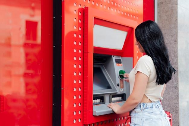Senior vrouw van middelbare leeftijd die contant geld aanneemt bij een geldautomaat op straat