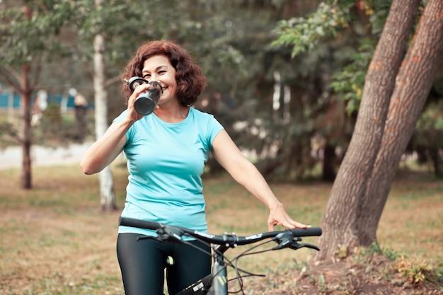 Senior vrouw van middelbare leeftijd op fietstocht in plattelandspark buiten en drink water uit de fles.