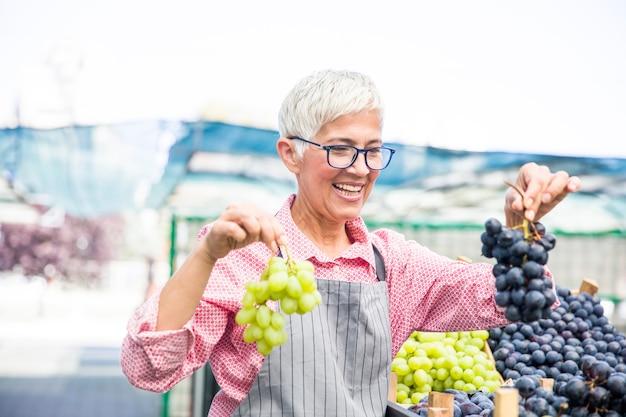 Senior vrouw verkoopt druiven op de markt