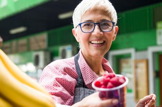 Senior vrouw verkoopt frambozen op de markt