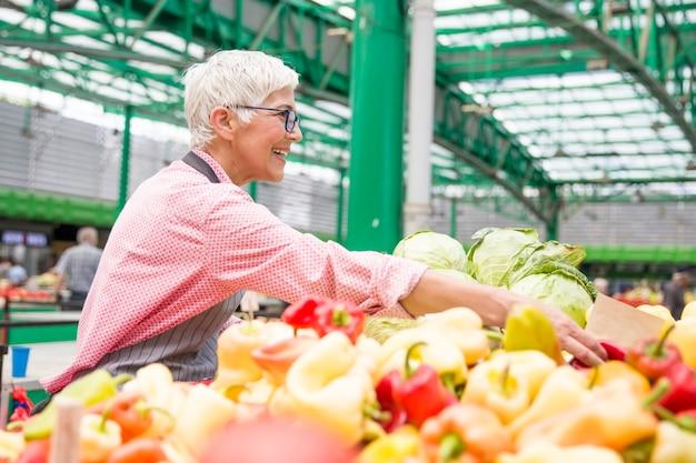 Senior vrouw verkoopt fruit op de markt