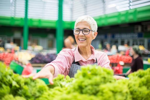 Senior vrouw verkoopt sla op de markt