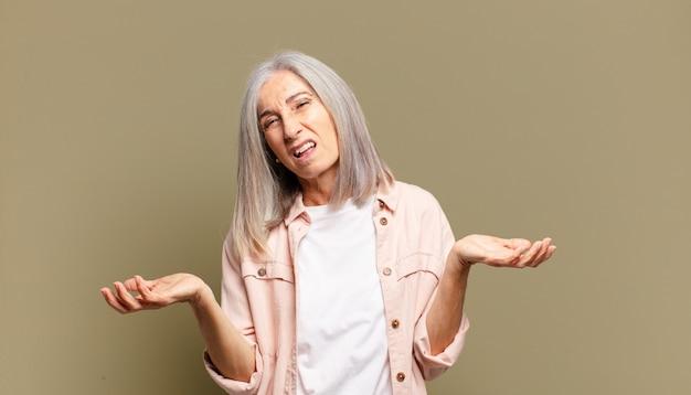 Senior vrouw voelt zich geen idee en verward, niet zeker welke keuze of optie ze moet kiezen, zich afvragend