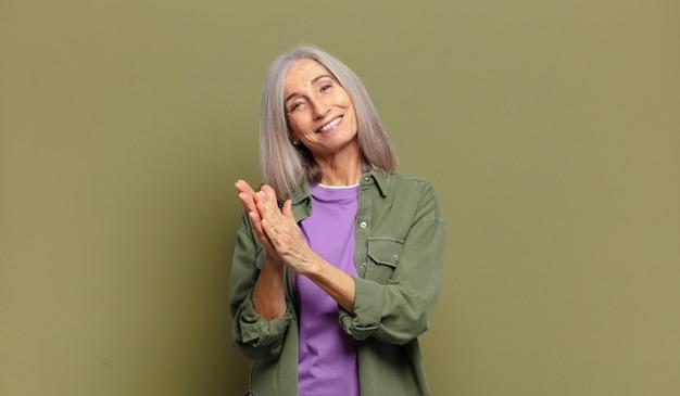 Senior vrouw voelt zich gelukkig en succesvol, lacht en klapt in de handen en zegt gefeliciteerd met een applaus