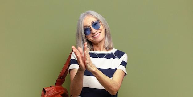 Senior vrouw voelt zich gelukkig en succesvol, lacht en klapt in de handen, zegt gefeliciteerd met een applaus
