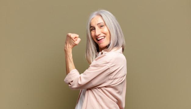 Senior vrouw voelt zich gelukkig, tevreden en krachtig, buigt fit en gespierde biceps, ziet er sterk uit na de sportschool