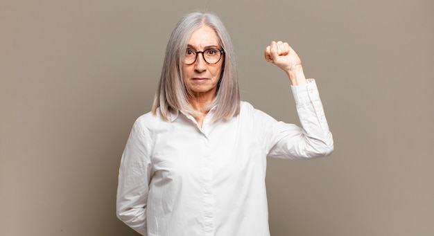 Senior vrouw voelt zich serieus, sterk en rebels, steekt haar vuist op, protesteert of vecht voor revolutie