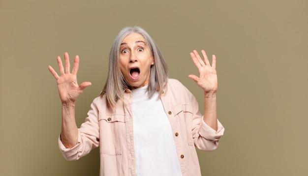 Senior vrouw voelt zich stomverbaasd en bang, bang voor iets beangstigend, met de handen open en zegt: blijf weg