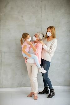 Senior vrouw, volwassen vrouw en schattig klein meisje, drie generaties met beschermende gezichtsmaskers thuis