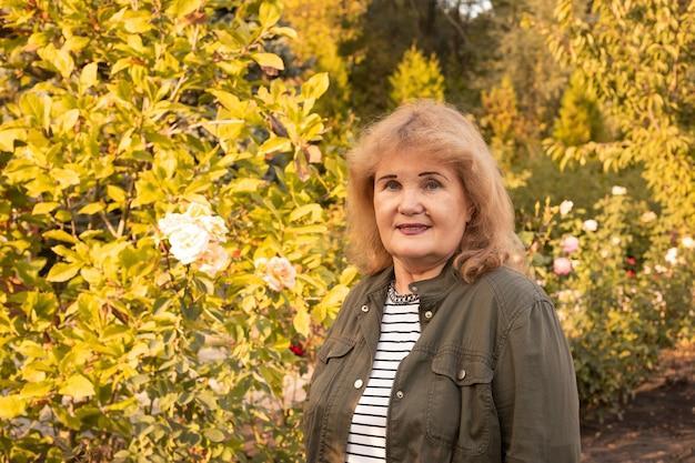 Senior vrouw wandelen in groen park, gelukkig pensioen