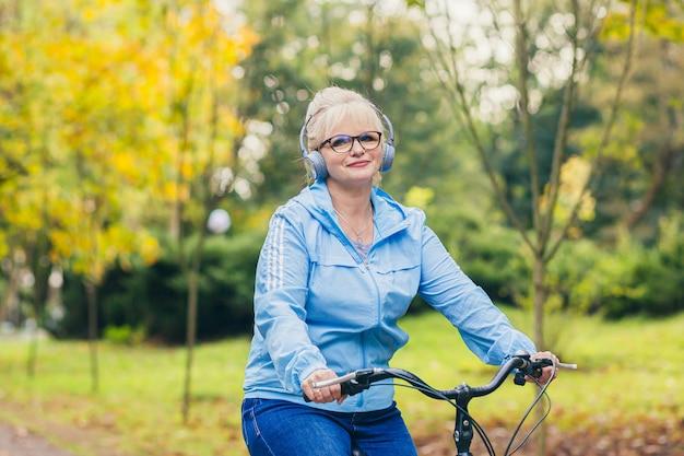 Senior vrouw wandelen in het park met een fiets
