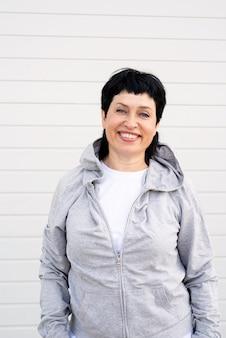 Senior vrouw waring grijs jasje staande buiten op grijze stevige muur
