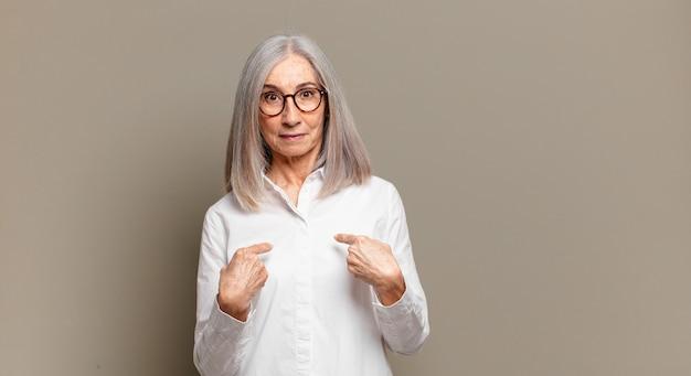 Senior vrouw wijzend naar zichzelf met een verwarde en vragende blik, geschokt en verrast om gekozen te worden