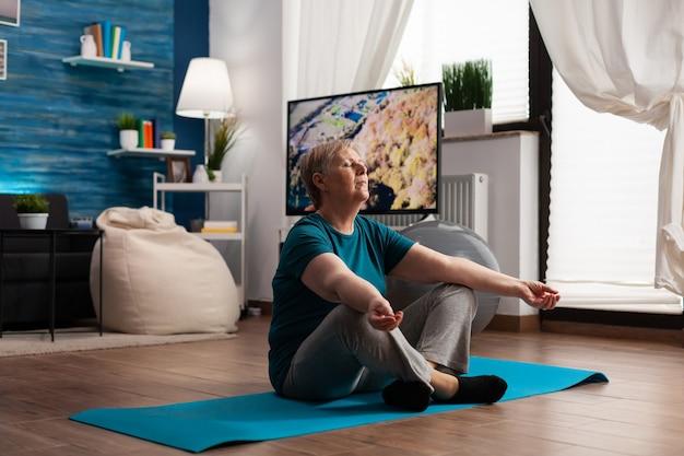 Senior vrouw zit comfortabel in lotushouding op yogamat met gesloten ogen
