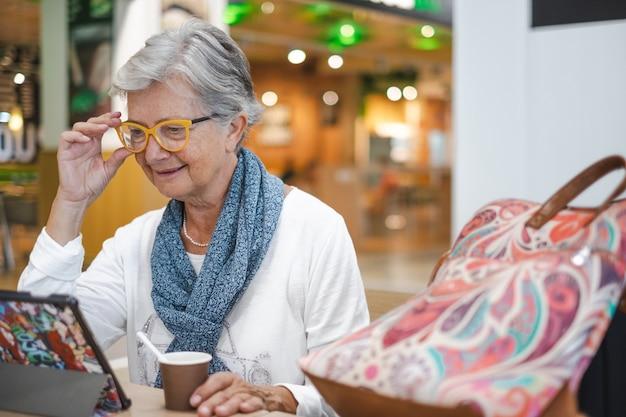 Senior vrouw zit in het luchthavencafé met behulp van een digitale tablet terwijl ze wacht op het instappen. gelukkige volwassen reiziger drinkt koffie