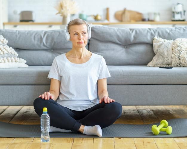 Senior vrouw zit met gekruiste benen in een koptelefoon en luistert naar muziek in de woonkamer