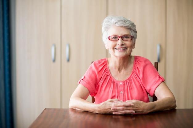 Senior vrouw zitten aan een tafel