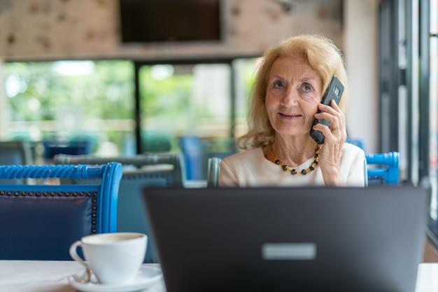 Senior vrouw zitten en met behulp van laptop computer en mobiele telefoon