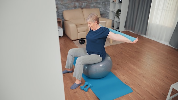 Senior vrouw zittend op balans bal training met weerstandsband. bejaarde training thuis sport gezonde levensstijl, ouderen fitness oefening workout in appartement, activiteit en gezondheidszorg