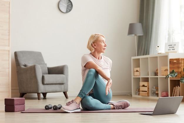 Senior vrouw zittend op de vloer op oefeningsmat voor laptop en training thuis