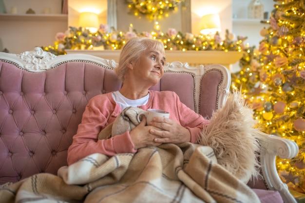 Senior vrouw zittend op een bank en op zoek attent