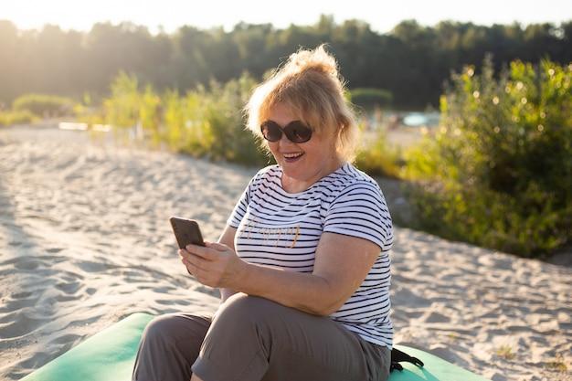 Senior vrouw zittend op een zand en het gebruik van smartphone in zomer-strand