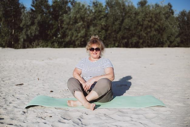 Senior vrouw zittend op een zand op zonnige dag