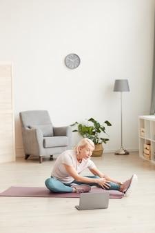 Senior vrouw zittend op oefeningsmat en haar benen strekken en kijken naar online sporttraining op laptop thuis