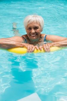 Senior vrouw zwemmen met opblaasbare buis in het zwembad