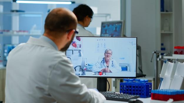 Senior vrouwelijke arts die medische online adviezen geeft aan chemicus met behulp van pc-webcam. wetenschapper houdt bloedmonster vast tijdens online discussie, virtuele conferentie, hulp bij telegeneeskunde, gezondheidszorgondersteuning