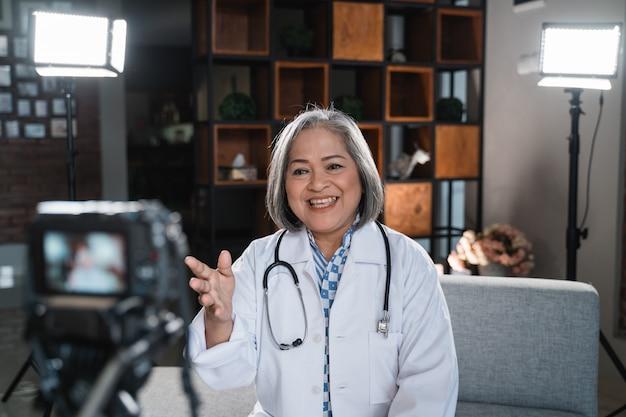 Senior vrouwelijke arts neemt een video op van haar blog
