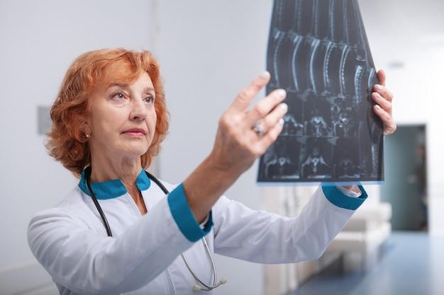 Senior vrouwelijke arts onderzoekt mri-scan van een patiënt