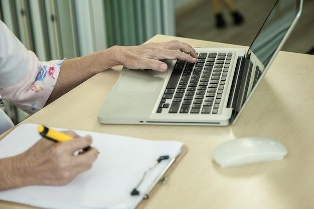 Senior vrouwelijke arts zittend op een bureau met een persoonlijke laptop