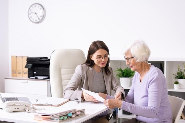 Senior vrouwelijke cliënt met wit haar verzekeringsformulier kijken en luisteren naar jonge agent haar uitleggen hoe het in te vullen