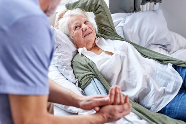 Senior vrouwelijke patiënt in het ziekenhuis met bezorgde echtgenoot hand in hand tijdens het controleren van de bloeddruk met tonometer. man helpt, ondersteunt