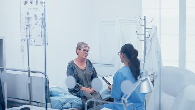 Senior vrouwelijke patiënt in ziekenhuisbed praten met verpleegster. schot door glazen raam. gezondheidszorg in een modern ziekenhuis of privékliniek, ziektepreventie en consultatie in medische behandelmedi