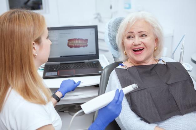 Senior vrouwelijke patiënt met tandheelkundige scan door haar tandarts in de kliniek