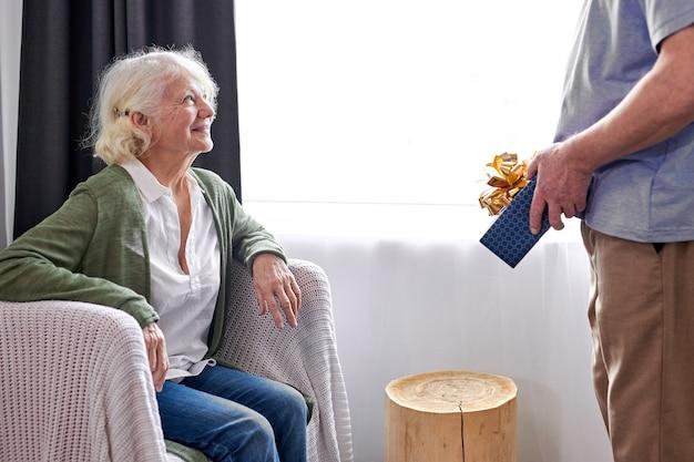 Senior vrouwelijke persoon met tevreden gezicht krijgt huidige doos door haar mooie knappe echtgenoot, grijsharige bejaarde echtpaar viert de verjaardag van de vrouw, man feliciteert haar
