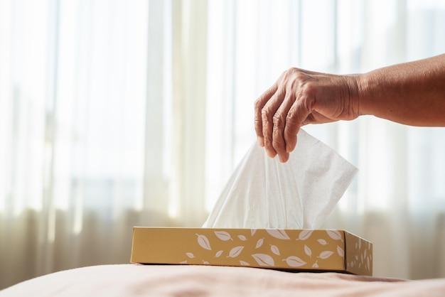 Senior vrouwen die servet / tissuepapier uit de tissuedoos met de hand plukken