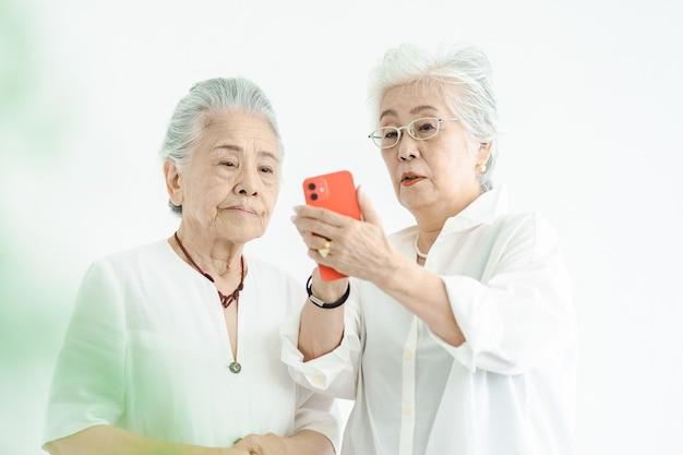 Senior vrouwen die smartphone bedienen met vallen en opstaan