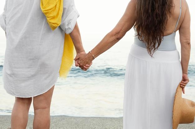 Senior vrouwen hand in hand op het strand