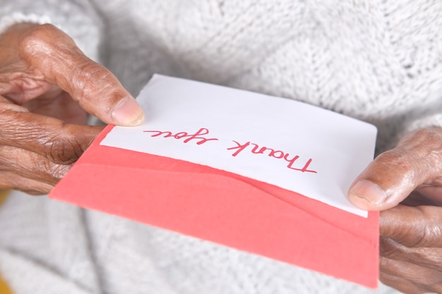Senior vrouwen hand met dank u brief achteraanzicht