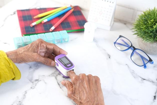 Senior vrouwen hand met pulsoximeter op tafel