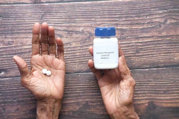 Senior vrouwen houden covid medische mediale pillen op tafel vast