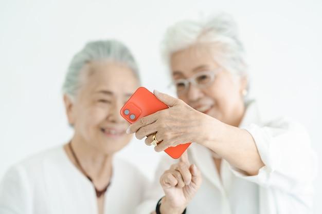 Senior vrouwen kijken met een glimlach naar smartphoneschermen