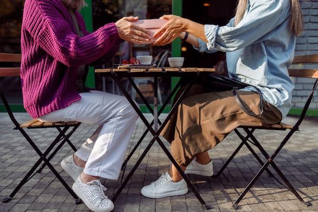 Senior vrouwenvrienden houden een geschenkdoos boven de tafel op het terras van een café
