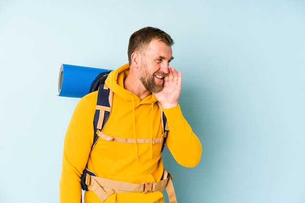 Senior wandelaar man geïsoleerd op blauwe achtergrond zegt een geheim heet remmend nieuws en kijkt opzij